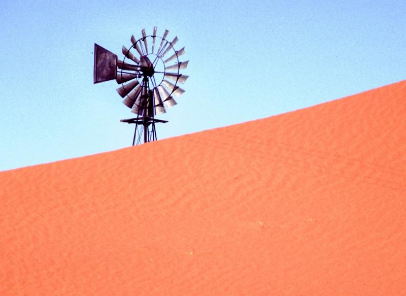 Südafrika Kalahari - Windrad schaut hinter Düne hervor