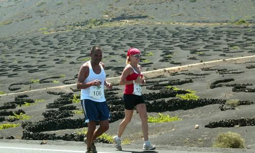 Hellgrüne Weinreben auf schwarzem Vulkanboden – beim Lanzarote WineRun laufen die Teilnehmer quer durch das Weinanbaugebiet la Geria. Bildnachweis: Turismo Lanzarote